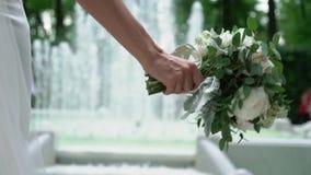 Brud med blommor nära springbrunnen arkivfilmer