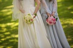 Brud med blommor och hembiträden Royaltyfri Bild
