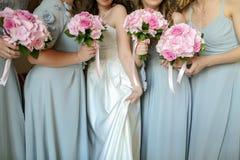 Brud med blommor och hembiträden Royaltyfria Bilder