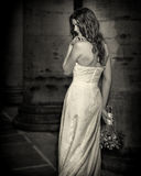 Brud med bröllopblommabuketten i den vita klänningen med bröllopfrisyren och makeup Le kvinnan i bröllopsklänningen som väntar på Royaltyfri Bild