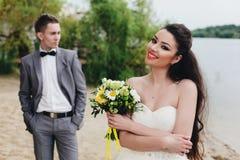 Brud med brudgummen bakom på flodbanken Arkivbild