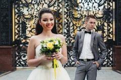 Brud med buketten och brudgum på bakgrunden Royaltyfria Bilder