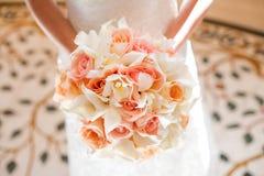 Brud med den härliga apelsin- och rosa färgbröllopbuketten av blommor Arkivfoton