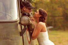 Brud med hennes bärande armédräkt för brudgum Arkivfoto