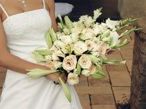 Brud med kräm- ro och liljar Arkivfoto