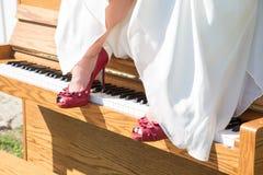Brud med röda skor på piano royaltyfria bilder