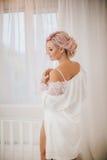 Brud med stilfullt smink i den vita klänningen Arkivfoton