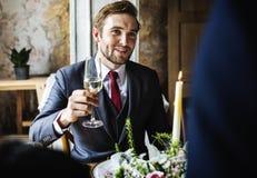 Brud och brudgum Clinging Wineglasses med vänner på att gifta sig Rec Arkivbilder