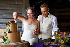 Brud och brudgum Cutting Wedding Cake royaltyfria bilder