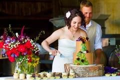 Brud och brudgum Cutting Wedding Cake arkivbilder