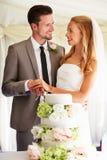 Brud och brudgum Cutting Wedding Cake på mottagandet Arkivbilder