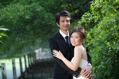 Brud och brudgum Embrace i trädgården Arkivbild