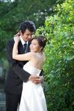 Brud och brudgum Embrace i trädgården Arkivfoton
