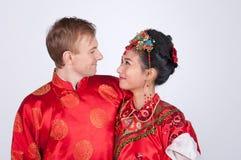 Brud och brudgum för blandat lopp i studion som bär bröllopdräkter för traditionell kines Royaltyfri Bild