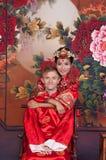 Brud och brudgum för blandat lopp i studion som bär bröllopdräkter för traditionell kines Royaltyfri Fotografi