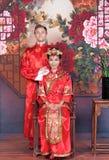 Brud och brudgum för blandat lopp i studion som bär bröllopdräkter för traditionell kines Arkivbilder