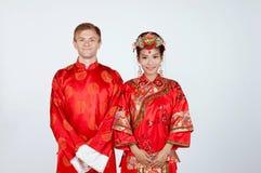 Brud och brudgum för blandat lopp i studion som bär bröllopdräkter för traditionell kines Royaltyfria Bilder