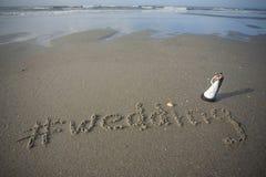 Brud och brudgum Figurine på stranden med att gifta sig som är skriftligt i sanden royaltyfria foton