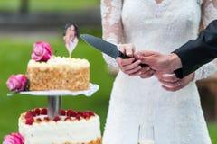 Brud och brudgum framme av bröllopstårtan arkivfoto
