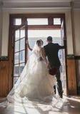 Brud och brudgum framme av tappningdörrar fotografering för bildbyråer
