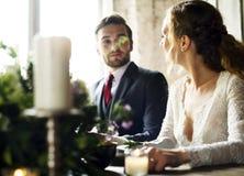 Brud och brudgum Having Meal med vänner på bröllopmottagandet royaltyfri bild