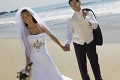 Brud och brudgum Holding Hands While som går på stranden royaltyfria bilder