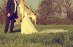Brud och brudgum i en solig dag på som sparas med ett hus i bakgrunden Royaltyfria Bilder