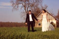 Brud och brudgum i en solig dag på som sparas med ett hus i bakgrunden Arkivfoto