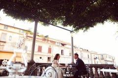 Brud och brudgum i en utomhus- restaurang Arkivbild