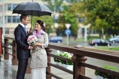Brud och brudgum i ett regnigt väder Fotografering för Bildbyråer