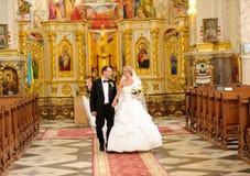 Brud och brudgum i kyrkan Arkivfoto