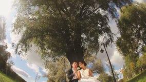Brud och brudgum i parkera med godisar i händer lager videofilmer