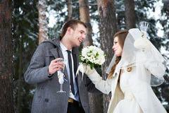 Brud och brudgum med champagneexponeringsglas i vinterskog Arkivbild