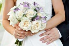 Brud och brudgum med den färgrika buketten Arkivbilder