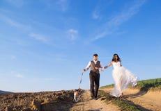 Brud och brudgum med hunden Royaltyfria Bilder