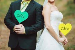 Brud och brudgum med kort i form av hjärta Arkivbilder