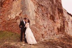 Brud och brudgum mot en bricked vägg arkivbilder