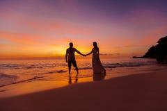 Brud och brudgum på en tropisk strand med solnedgången i backgen Arkivbild