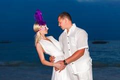 Brud och brudgum på en tropisk strand med solnedgången i backgen Royaltyfri Bild