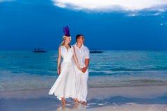 Brud och brudgum på en tropisk strand med solnedgången i backgen Royaltyfri Foto