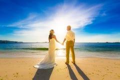 Brud och brudgum på en tropisk strand med solnedgången i backgen Royaltyfria Bilder