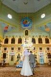 Brud och brudgum på kyrkan under en bröllopceremoni arkivfoto