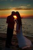 Brud och brudgum på solnedgången Arkivbild