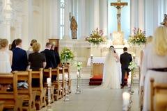Brud och brudgum på kyrkan under ett bröllop Arkivfoto