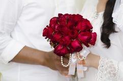 Brud och brudgum With Red Rose Bouquet Arkivbild