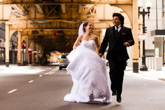 Brud och brudgum Running Under Bridge Arkivbilder