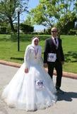 Brud och brudgum som är klara för maraton med dräkten på den orange blomningkarnevalet royaltyfria foton
