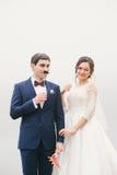 Brud och brudgum som fästas för att vända mot den pappers- mustaschen, exponeringsglas Royaltyfria Foton