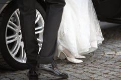 Brud och brudgum som får ut ur bilen Royaltyfria Bilder