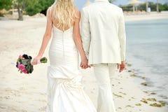 Brud och brudgum som går handen - in - hand Fotografering för Bildbyråer